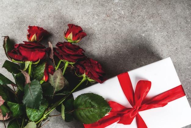 Vakantieachtergrond, valentijnsdag. boeket rode rozen, stropdas met een rood lint, met ingepakte geschenkdoos en rode kaars bovenaanzicht