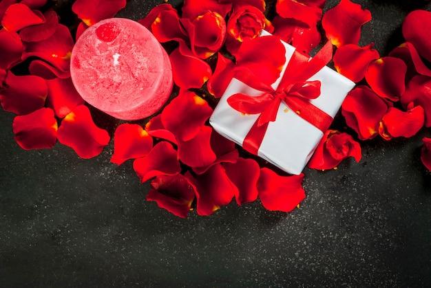 Vakantieachtergrond, valentijnsdag. boeket rode rozen, stropdas met een rood lint, met ingepakte geschenkdoos en rode kaars