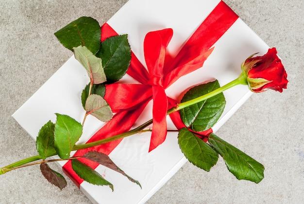 Vakantieachtergrond, valentijnsdag. verpakte geschenkdoos met een rode roos bovenaanzicht