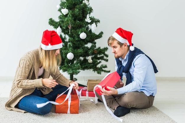 Vakantieconcept - lief paar dat kerstcadeaus opent, zittend in de woonkamer.