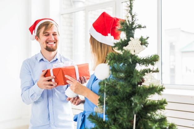 Vakantieconcept - man die een kerstcadeau geeft aan zijn vriendin.