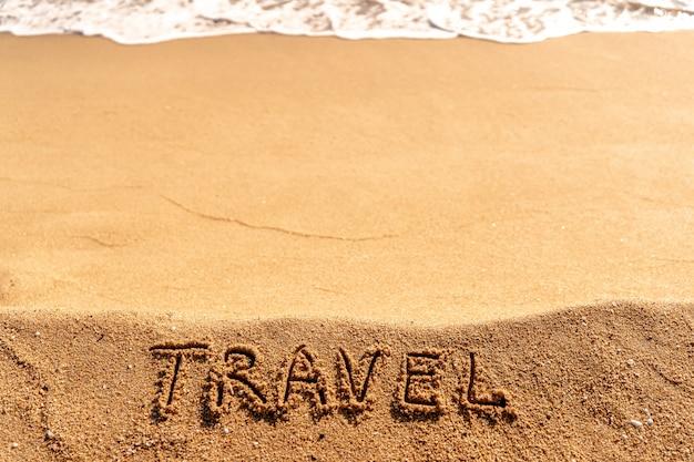 Vakantieconcept op het strand. word travel geschreven op het zand in de buurt van de zee.