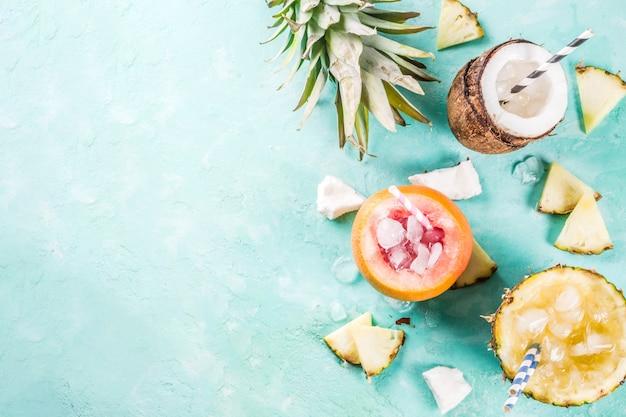 Vakantiedrank concept, stel verschillende tropische cocktails of sappen in ananas, grapefruit en kokosnoot met ijs