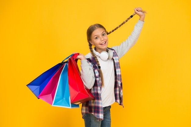 Vakantiegeschenken in pakketten. cyber maandag. schiet op met de totale verkoop. kinder mode. verkoop en kortingen. gelukkig klein meisje na succesvol winkelen. schattig kind met zware tassen. beste outfit ooit.