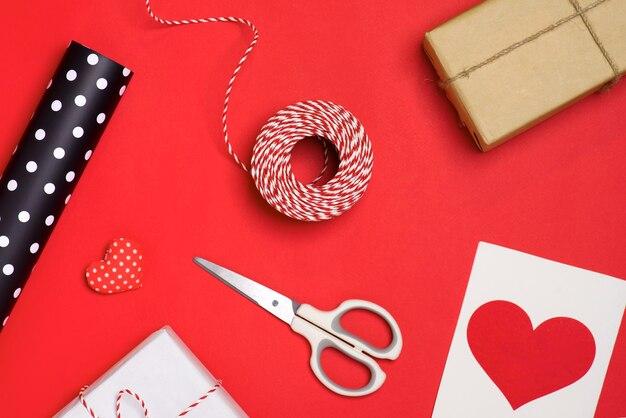 Vakantiegeschenken inpakken voor valentijnsdag op rode achtergrond.