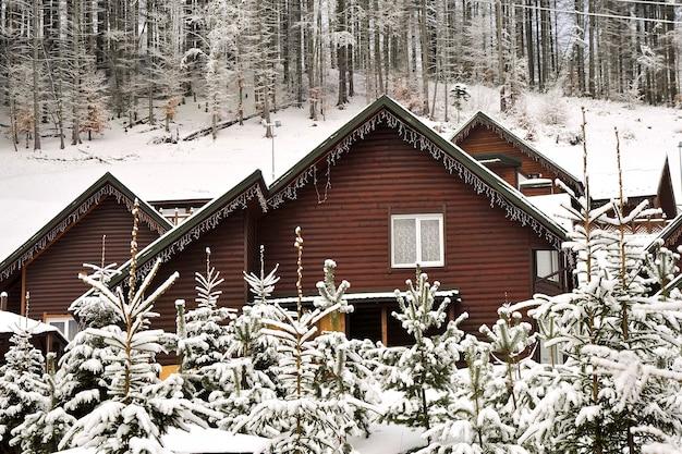 Vakantiehuis in vakantieoord in de bergen bedekt met verse sneeuw in de winter. houten huisje.