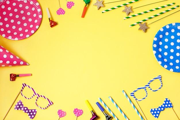 Vakantiekader of achtergrond met papieren borden en rietjes, hoorns, grappige glazen, carnaval pet en streamer
