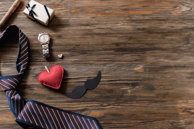 Vakantiekader van geschenkdozen, snor, papieren hoed, pijp, stropdas en klok op oude houten tafel.