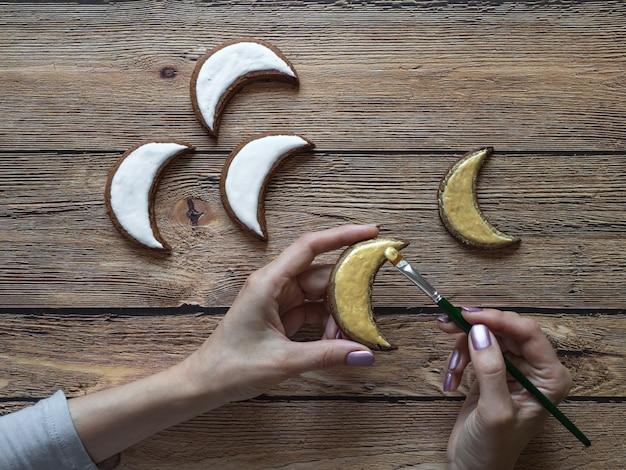 Vakantiekoekjes koken in ramadan. goud geschilderde koekjes in de vorm van een halve maan.