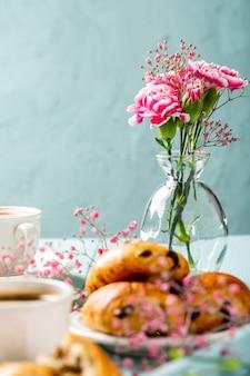 Vakantiepauze met kopje koffie, mini vers chocoladebroodje croissants en anjerbloemen op turkoois oppervlak. kopieer ruimte