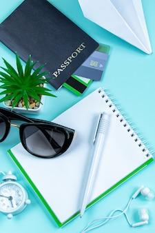 Vakantieplanning reisaccessoires op een blauwe achtergrond paspoortzonnebril en notitieblok