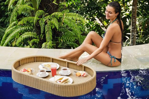 Vakanties in het resort. jonge gelukkige vrouw met een drijvend ontbijt in het zwembad.
