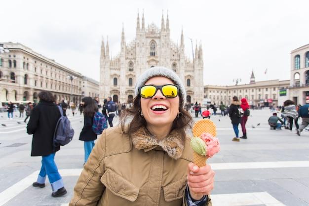 Vakanties, italië en winterreisconcept - jonge grappige vrouwelijke reiziger houdt ijs-ijsje staande voor de duomo-kathedraal in milaan.