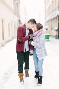 Vakanties, winter, warme dranken en mensen - een afbeelding van het paar dat in de winter in de oude stad loopt