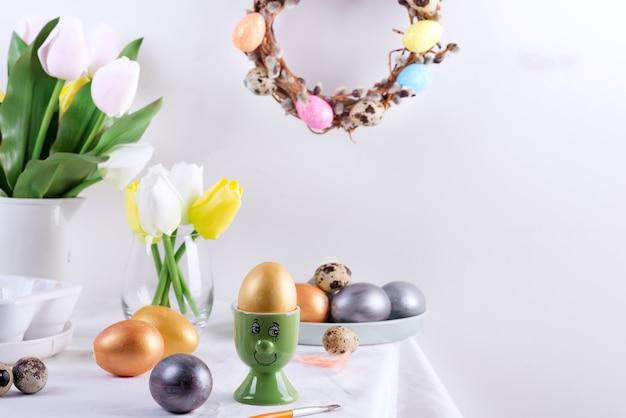 Vakantiesamenstelling van gediende lijst met gouden ei in een groene kop als gezicht, gebakken koekjes, de verse bloemen van de lentetulpen en feestelijke kroon op een lichtgrijze muur. happy easter concept.