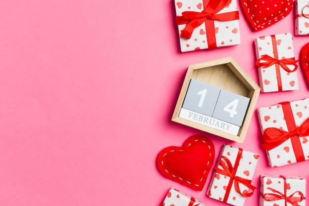 Vakantiesamenstelling van geschenkdozen, houten kalender en rode textielharten op kleurrijk de veertiende februari. bovenaanzicht van valentijnsdag