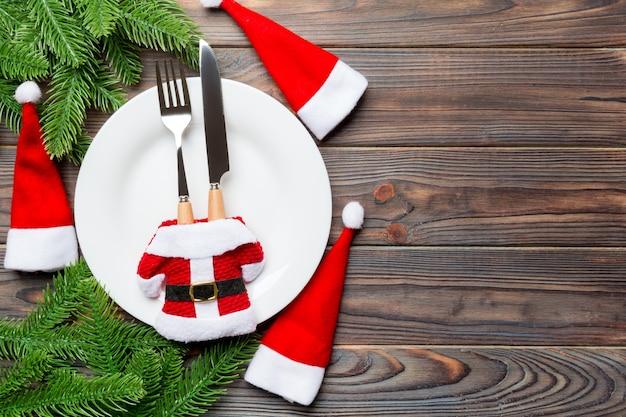 Vakantiesamenstelling van plaat en tafelgereedschap met kerstmanhoed en kleren wordt verfraaid op houten achtergrond die