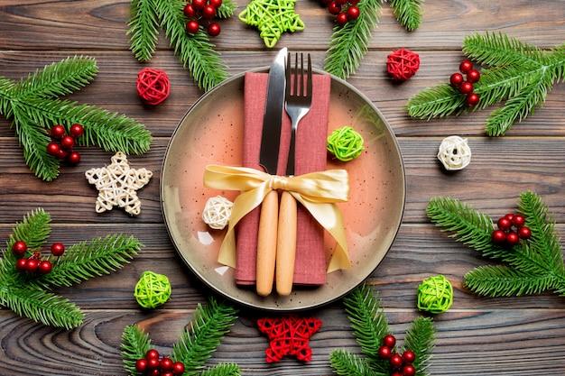 Vakantiesamenstelling van plaat en tafelgereedschap met kerstmanhoed wordt verfraaid op houten achtergrond die
