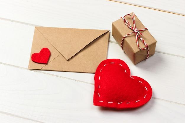 Vakantiespot omhoog: geschenkdozen, rood hart en blanco papier in bruine envelop. liefde concept. tekst ruimte