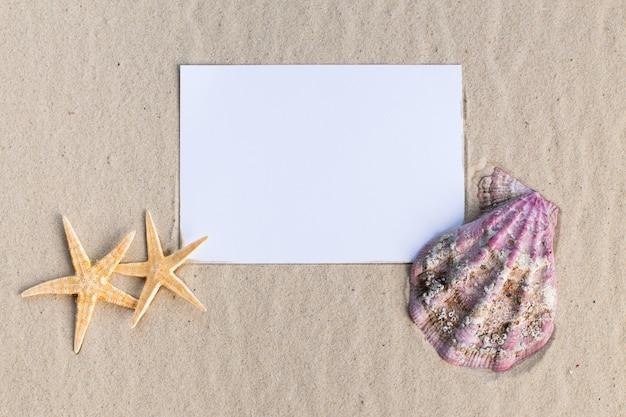 Vakantiestrand concept met schelpen, seastars en een lege ansichtkaart