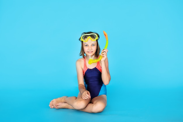 Vakantiethema: kindmeisje met snorkel- of duikuitrusting op een blauwe muur. avontuur en rust concept
