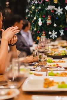 Vakantievieringsconcept vrienden die een kerstdiner hebben en binnen rode wijn drinken