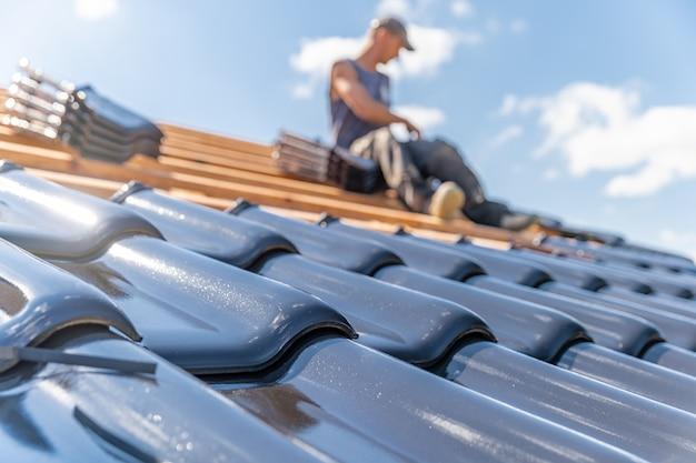 Vakman koestert een gebakken keramische tegel op het dak