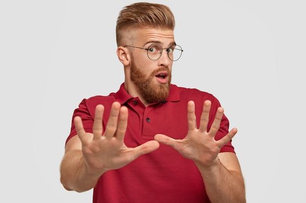 Val me alsjeblieft niet lastig! verrast emotionele gember bebaarde jonge kerel maakt stop-gebaar, streelt handen, voelt zich ontevreden, draagt casual rood t-shirt, geïsoleerd over witte muur.