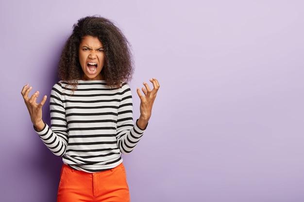 Val me niet lastig! woedende afro-vrouw gebaart boos en schreeuwt naar iemand
