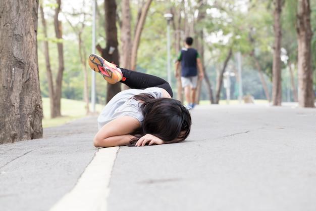 Val van een vrouw tijdens het hardlopen in het park