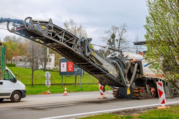 Valasske mezirici, tsjechië, 23 april 2019: freesmachine verwijdert oud asfalt van de weg.
