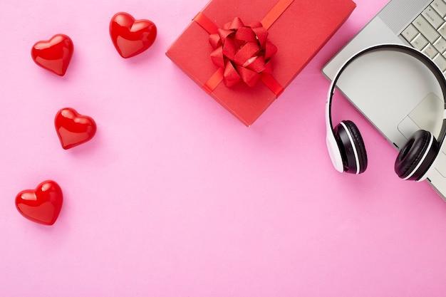 Valentijn cadeau in vakantie decoratie copyspace rode geschenkdoos met een rode strik op een roze achtergrond met rode harten holiday web banner