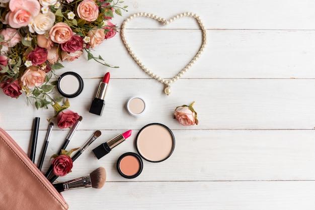 Valentijn cadeau. make-up cosmetica gereedschappen achtergrond- en schoonheidscosmetica, producten en gezichtscosmetica pakket lippenstift, oogschaduw met bloemroos, parelketting, vintage toon.