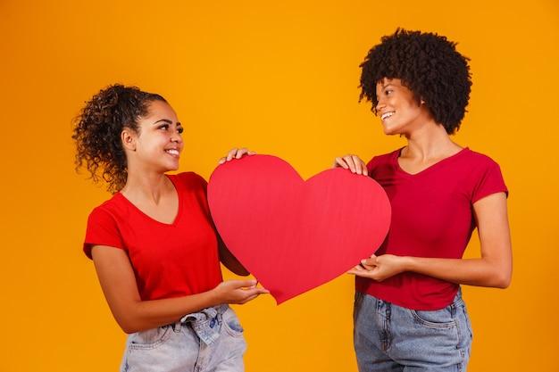 Valentijn lesbisch koppel met een papieren hart. valentijnsdag concept