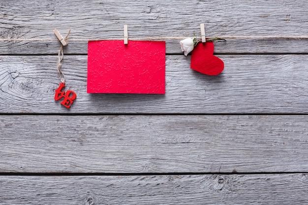 Valentijn met rood papier hart en lege wenskaart op wasknijpers op rustieke houten planken