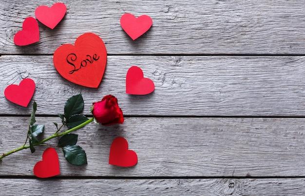 Valentijn met rood roze bloem, handgeschept papier harten en kaart op rustiek hout