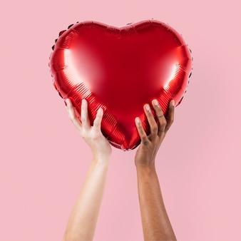 Valentijns hartballon vastgehouden door een persoon