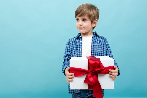 Valentijnsdag . aantrekkelijk kind heeft een groot geschenk met een rood lint op een lichtblauw