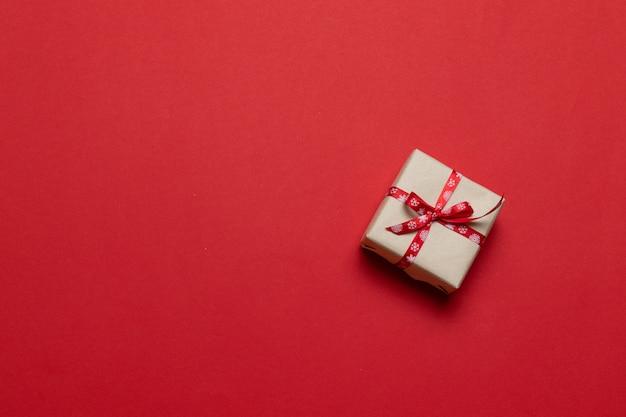 Valentijnsdag achtergrond. geschenk of huidige vak op rode tafel. trendy compositie voor verjaardag, moeder- of vaderdag. plat lag, bovenaanzicht, kopie ruimte