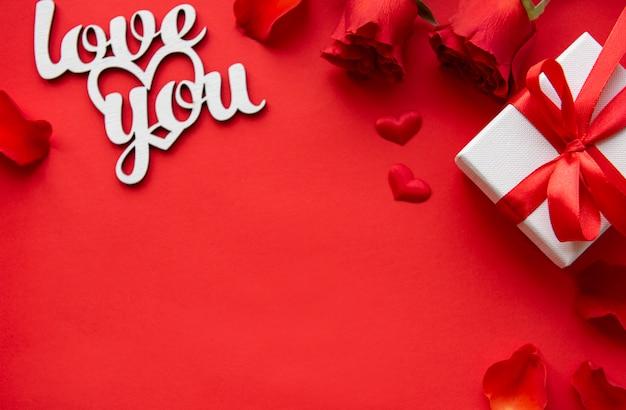 Valentijnsdag achtergrond met cadeau, rode roos en bericht