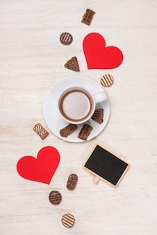 Valentijnsdag achtergrond met chocolade ballen, koffiekopje, rode harten en notebook