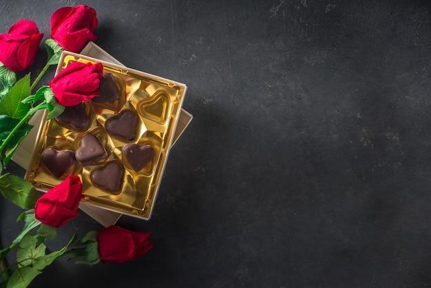 Valentijnsdag achtergrond met chocolade harten en rode rozen