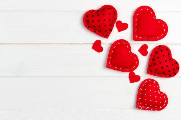 Valentijnsdag achtergrond met handgemaakte speelgoed harten op houten tafel