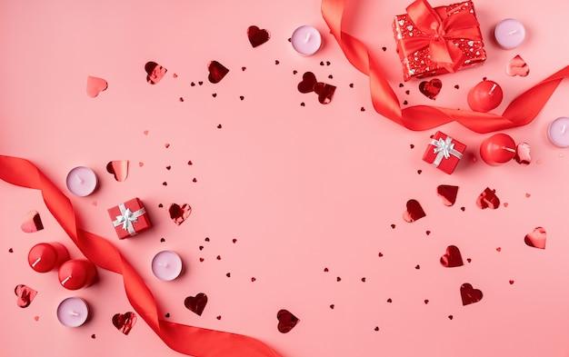 Valentijnsdag achtergrond met kaarsen, geschenken, harten en confetti bovenaanzicht plat lag
