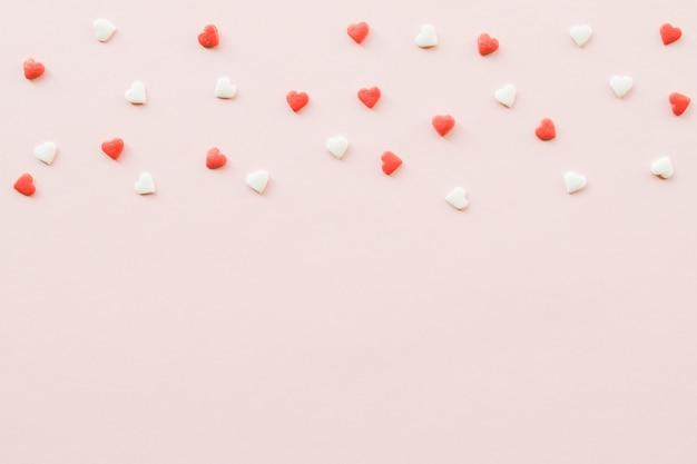 Valentijnsdag achtergrond met rode en witte kleine harten op roze achtergrond.