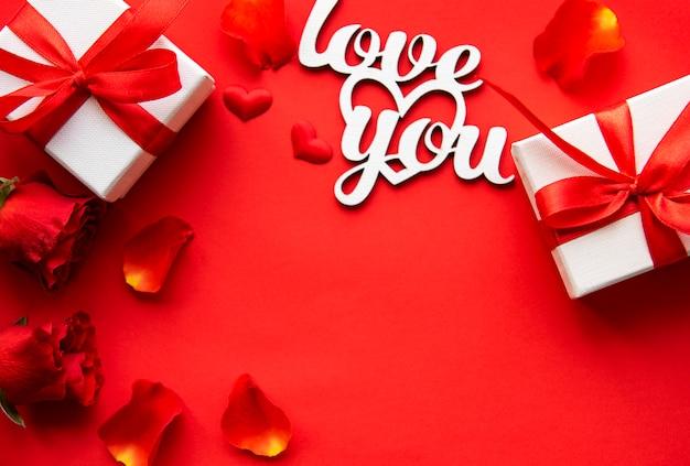 Valentijnsdag achtergrond met rode rozen, bloemblaadjes, geschenkdozen en tekst
