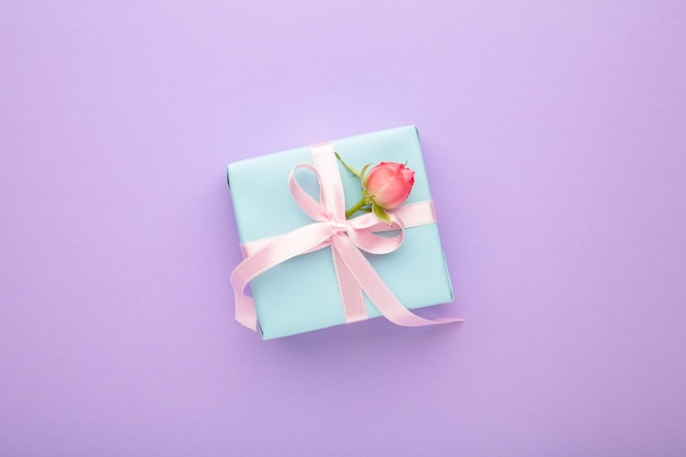 Valentijnsdag achtergrond met roze roos en geschenkdoos op paarse achtergrond. bovenaanzicht met kopie ruimte.