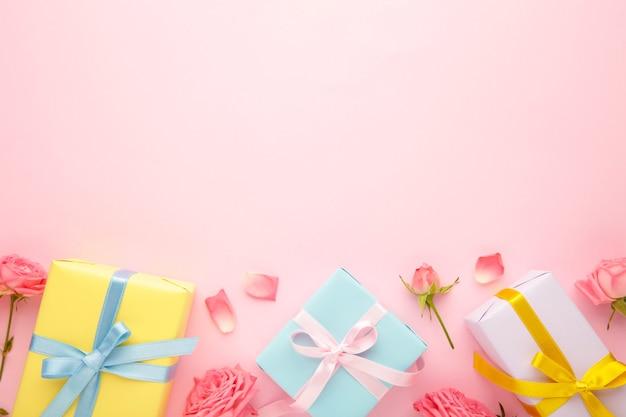 Valentijnsdag achtergrond met roze rozen en geschenkdoos op roze achtergrond. bovenaanzicht met kopie ruimte.
