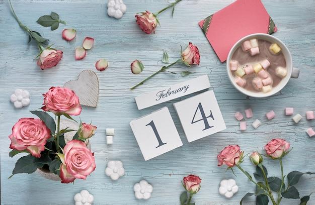 Valentijnsdag achtergrond met roze rozen, houten kalender, wenskaart en decoraties.