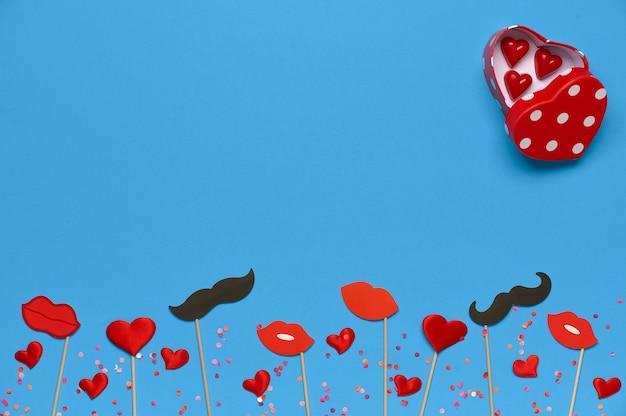 Valentijnsdag achtergrond met snoep doos in hartvorm, rode lippen, cadeau, decor op blauwe achtergrond met kopie ruimte. bovenaanzicht, plat gelegd